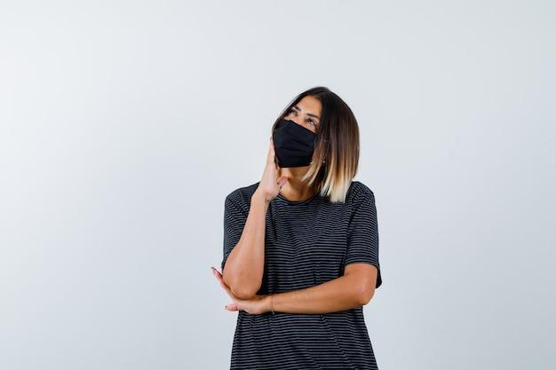 Jonge vrouw, kin leunend op palm, denken over iets in zwarte jurk, zwart masker en peinzend, vooraanzicht kijken.