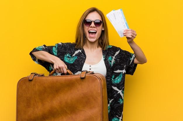 Jonge vrouw klaar om naar vakantie over gele achtergrond te gaan