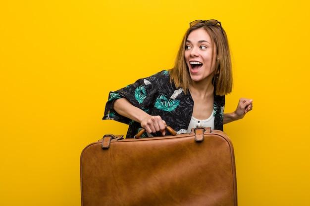 Jonge vrouw klaar om op vakantie te gaan op geel