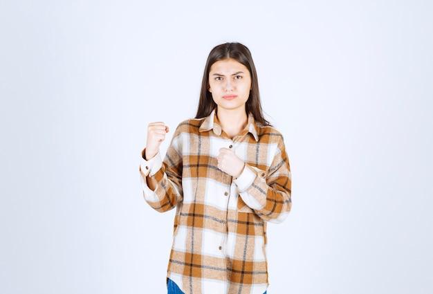 Jonge vrouw klaar voor strijd op witte muur.
