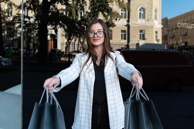 Jonge vrouw klant met papieren zakken. meisje shopaholic. black friday, verkoop, korting.
