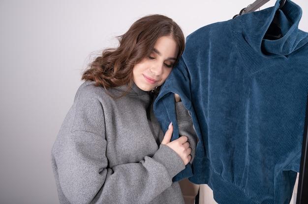 Jonge vrouw kleren in moderne winkel kiezen