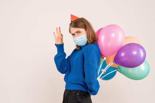Jonge vrouw kleurrijke ballonnen achter haar rug op wit verbergen