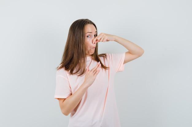 Jonge vrouw knijpen neus als gevolg van slechte geur in roze t-shirt en walgt, vooraanzicht.
