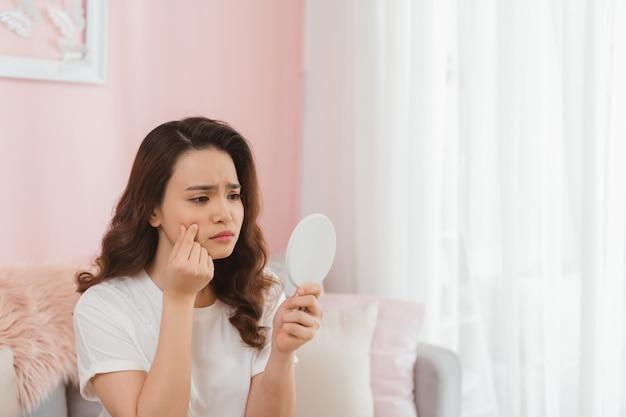 Jonge vrouw knijpen puistjes voor spiegel