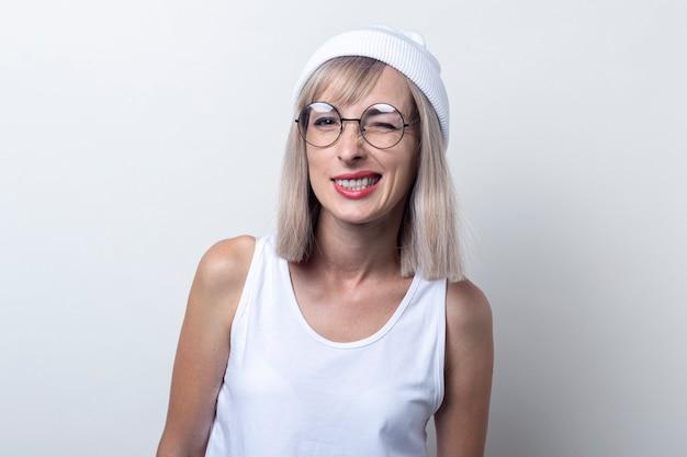 Jonge vrouw knipoogt in glazen, een witte hoed op een lichte achtergrond.