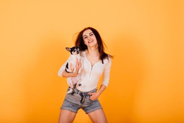 Jonge vrouw knuffelen chihuahua puppy in studio, geïsoleerd