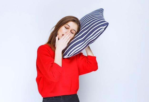 Jonge vrouw knuffelen een blauw gestreept kussen en slapen.