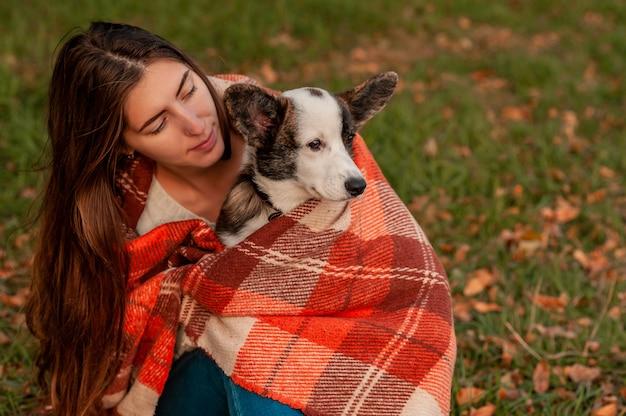 Jonge vrouw knuffelen haar welsh corgi hond in het najaar park