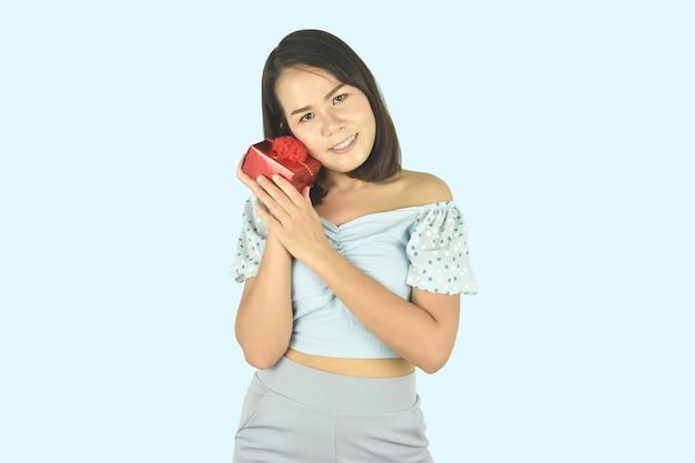 Jonge vrouw knuffelen rode geschenkdoos aanwezig voor verjaardag valentijn dag kerstmis nieuwjaar concept Premium Foto
