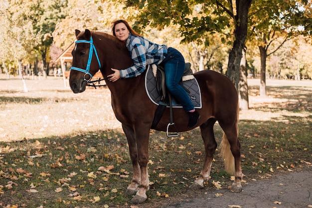 Jonge vrouw knuffelt een paard terwijl ze op straat loopt