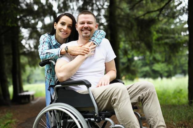 Jonge vrouw knuffelt gehandicapte man in rolstoel tijdens wandeling in park