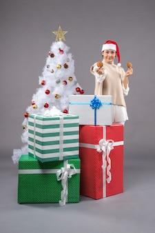 Jonge vrouw koekjes eten op grijze vloer in de buurt van kerstboom en geschenken