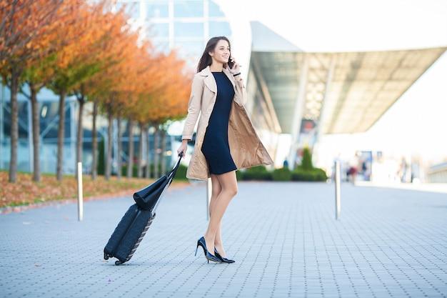 Jonge vrouw koffer trekken in de buurt van de luchthaventerminal.