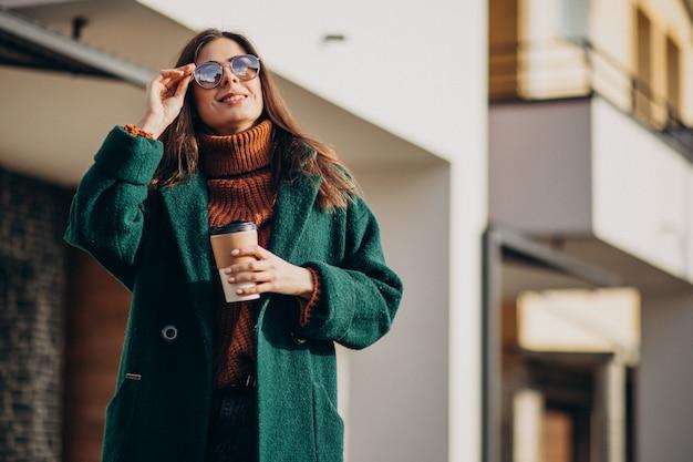 Jonge vrouw koffie drinken bij het huis