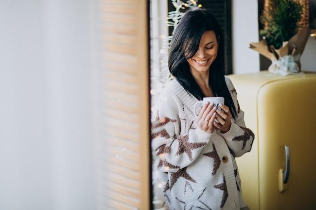 Jonge vrouw koffie drinken bij het raam