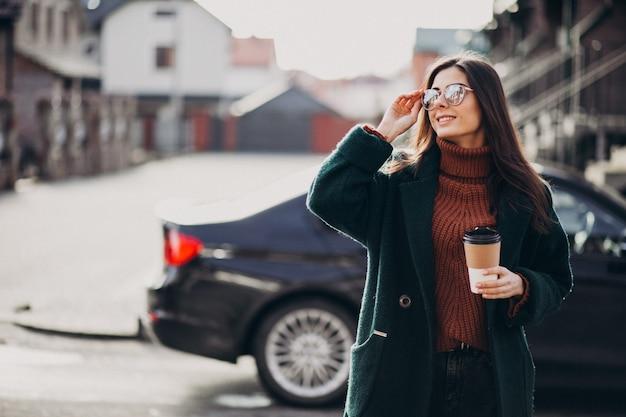 Jonge vrouw koffie drinken door haar auto
