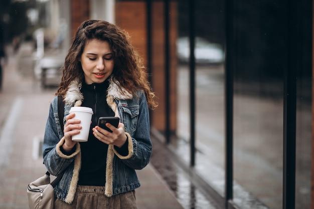 Jonge vrouw koffie drinken en het gebruik van de telefoon