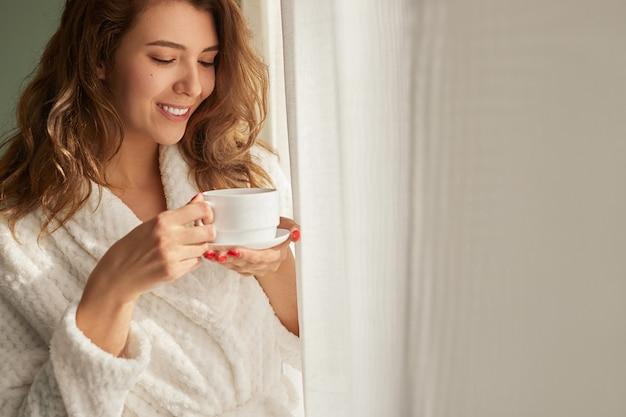 Jonge vrouw koffie drinken in de buurt van venster