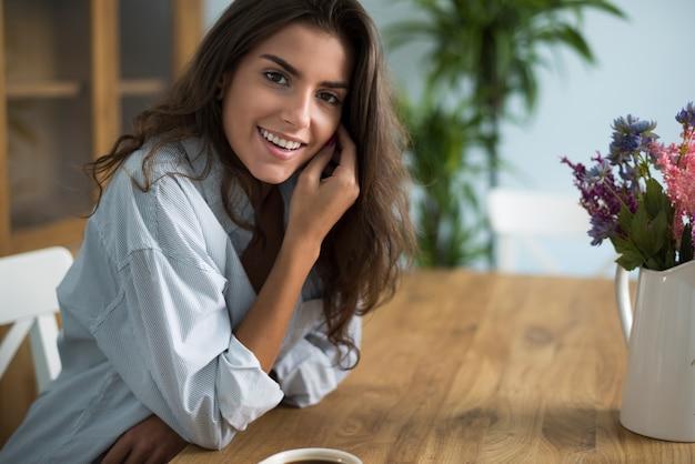 Jonge vrouw koffie drinken in de eetkamer