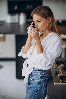 Jonge vrouw koffie drinken in de keuken