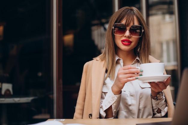 Jonge vrouw koffie drinken in een café op terras