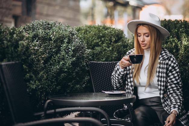 Jonge vrouw koffie drinken in een café