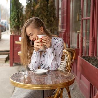 Jonge vrouw koffie drinken in een parijse straat café