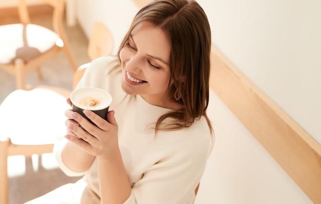 Jonge vrouw koffie drinken in gezellig café