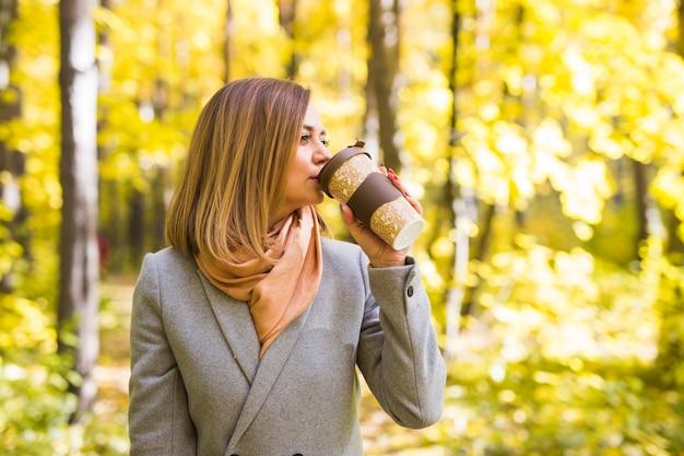 Jonge vrouw koffie drinken in herfst park