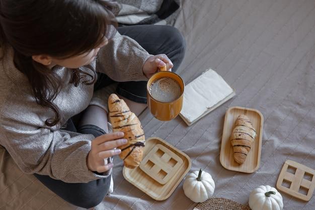 Jonge vrouw koffie drinken met een croissant in bed bovenaanzicht