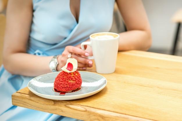 Jonge vrouw koffie drinken met een fluitje van een cent zittend aan tafel in een café buitenshuis