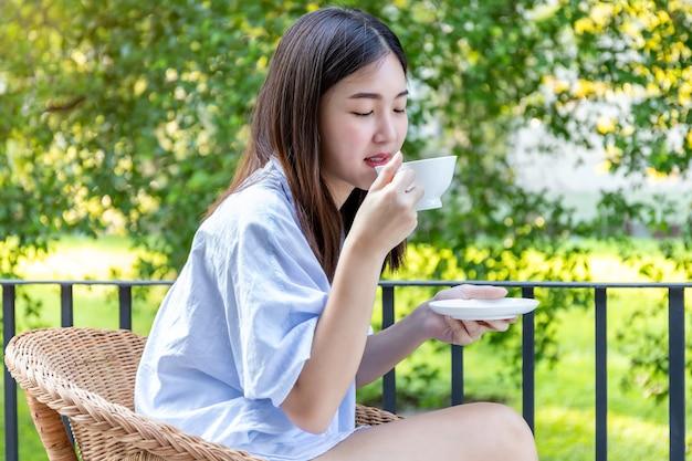 Jonge vrouw koffie drinken op balkon.