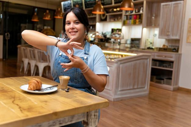 Jonge vrouw koffie drinken terwijl ze in gebarentaal spreekt