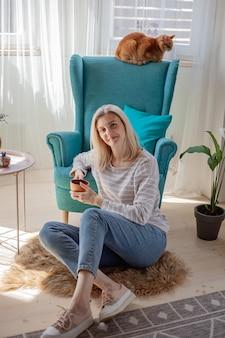 Jonge vrouw koffie drinken, zittend op de vloer naast fauteuil a