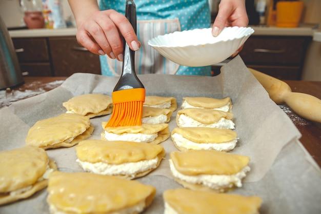 Jonge vrouw koken in de keuken, bereidt de taarten voor bakken
