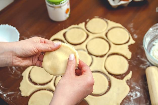 Jonge vrouw koken in de keuken, bereidt het deeg voor bakken