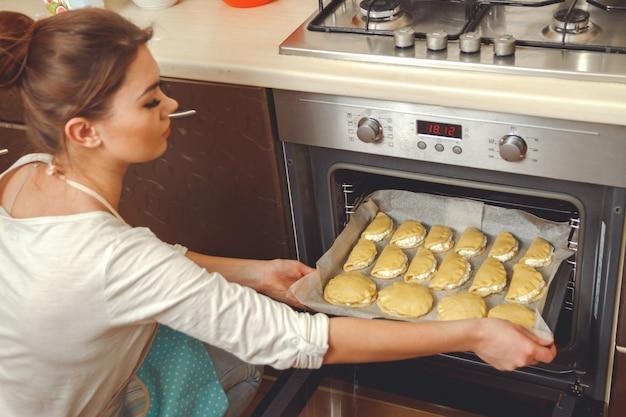 Jonge vrouw koken in de keuken, zet pasteitjes in de oven