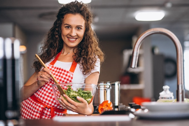 Jonge vrouw koken in de keuken