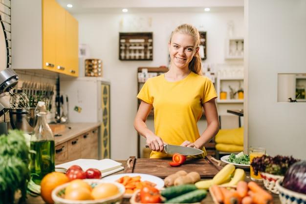 Jonge vrouw koken op recepten, gezond biovoedsel