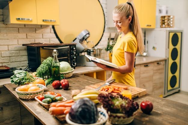 Jonge vrouw koken op recepten, gezond ecovoedsel