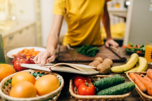 Jonge vrouw koken op recepten, gezonde biovoedsel voorbereiden.