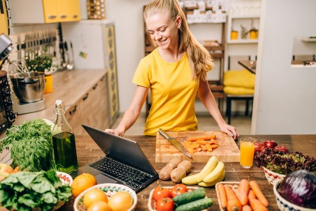 Jonge vrouw koken op recepten, gezonde voeding.