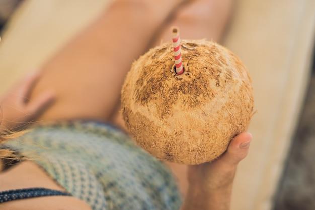 Jonge vrouw kokosmelk drinken op chaise-longue op strand