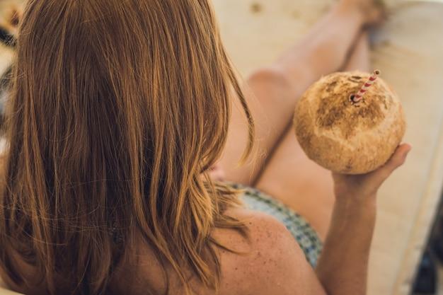 Jonge vrouw kokosmelk drinken op chaiselongue op strand