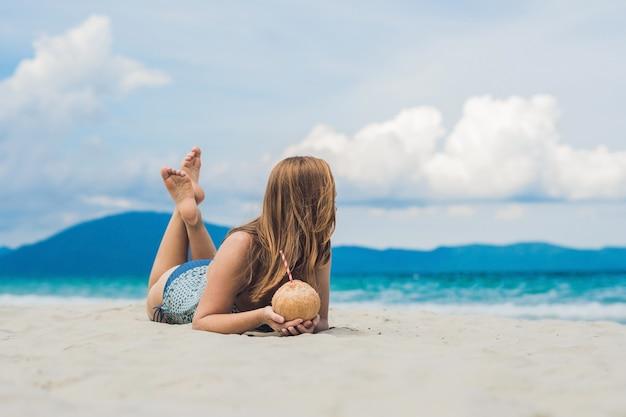 Jonge vrouw kokosmelk drinken op strand