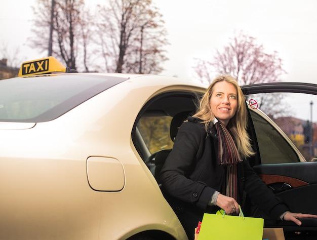 Jonge vrouw komt uit de taxi met boodschappentassen