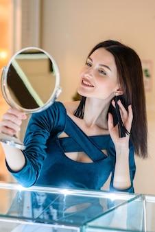 Jonge vrouw koopt oorbellen in de mall