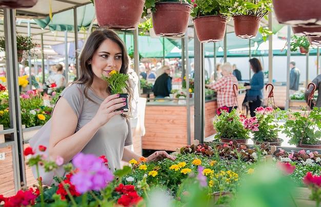 Jonge vrouw kopen bloemen in een tuincentrum. mijn favoriete bloemen. vrouw kijken naar bloemen in een winkel. portret van een lachende vrouw met bloemen in plantenkwekerij