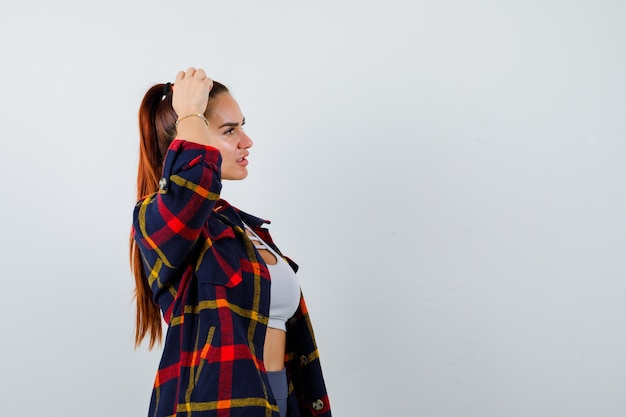 Jonge vrouw krabt hoofd in crop top, geruit hemd, broek en ziet er attent uit. vooraanzicht.